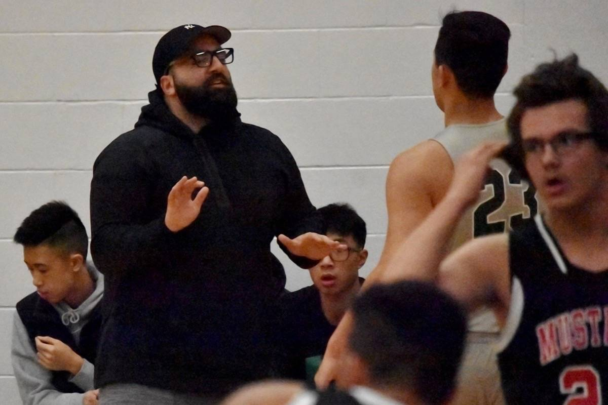 Yash Zandiyeh helps coach the Killarney Cougars against the Princess Margaret Mustangs from Penticton at Delview Secondary's inaugural Gurpreet Gill Invitational on Dec. 1, 2017. (James Smith photo)