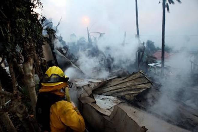 A firefighter hoses down smoldering debris in Ventura, Calif., Tuesday, Dec. 5, 2017. (Daniel Dreifuss via AP)