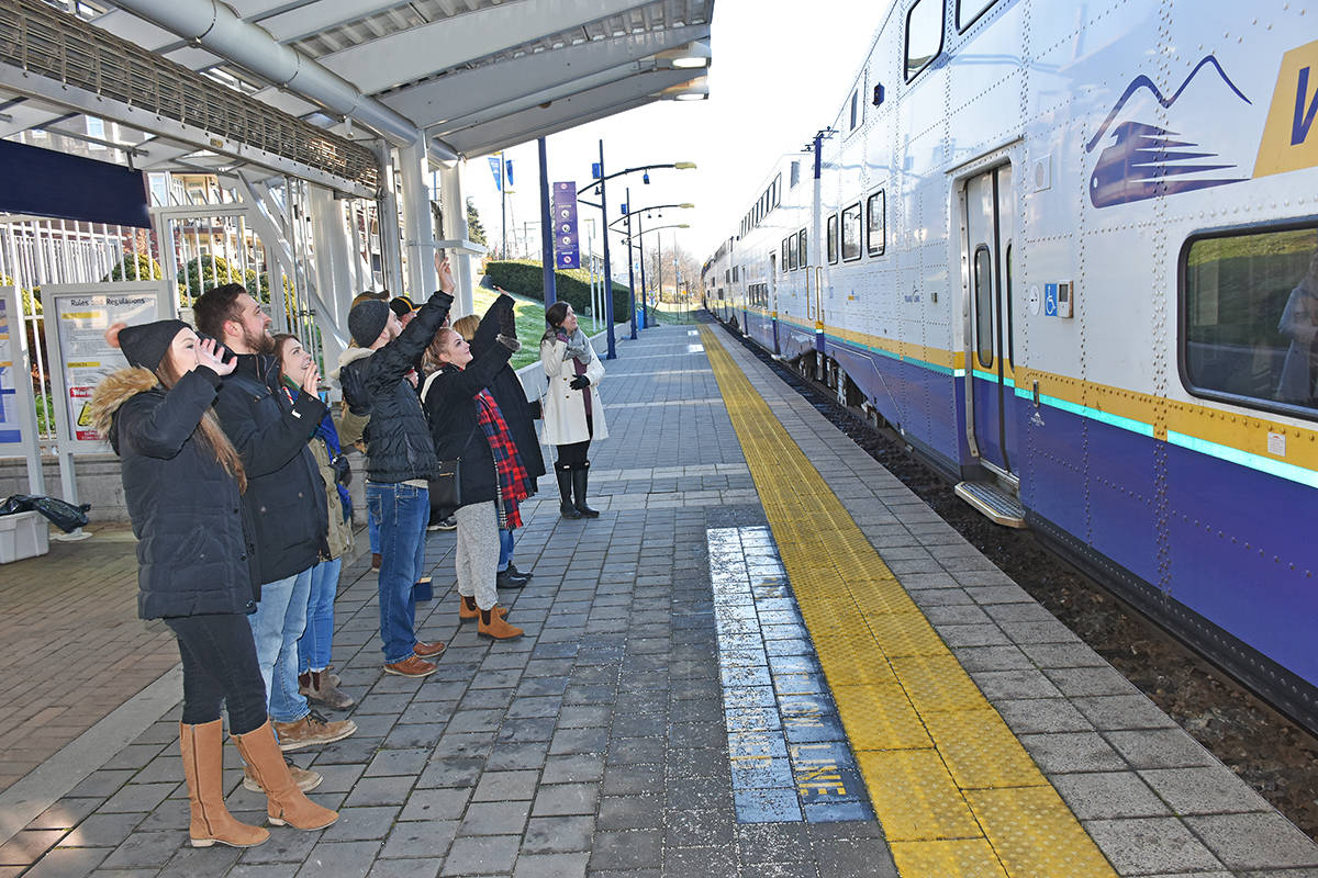 Volunteers for the Santa Train, which benefits the Christmas Hamper Society in Maple Ridge, wave to departing West Coast Express riders on their way for a day in Vancouver. The Santa Train train runs again on Dec. 16. (Neil Corbett/THE NEWS)