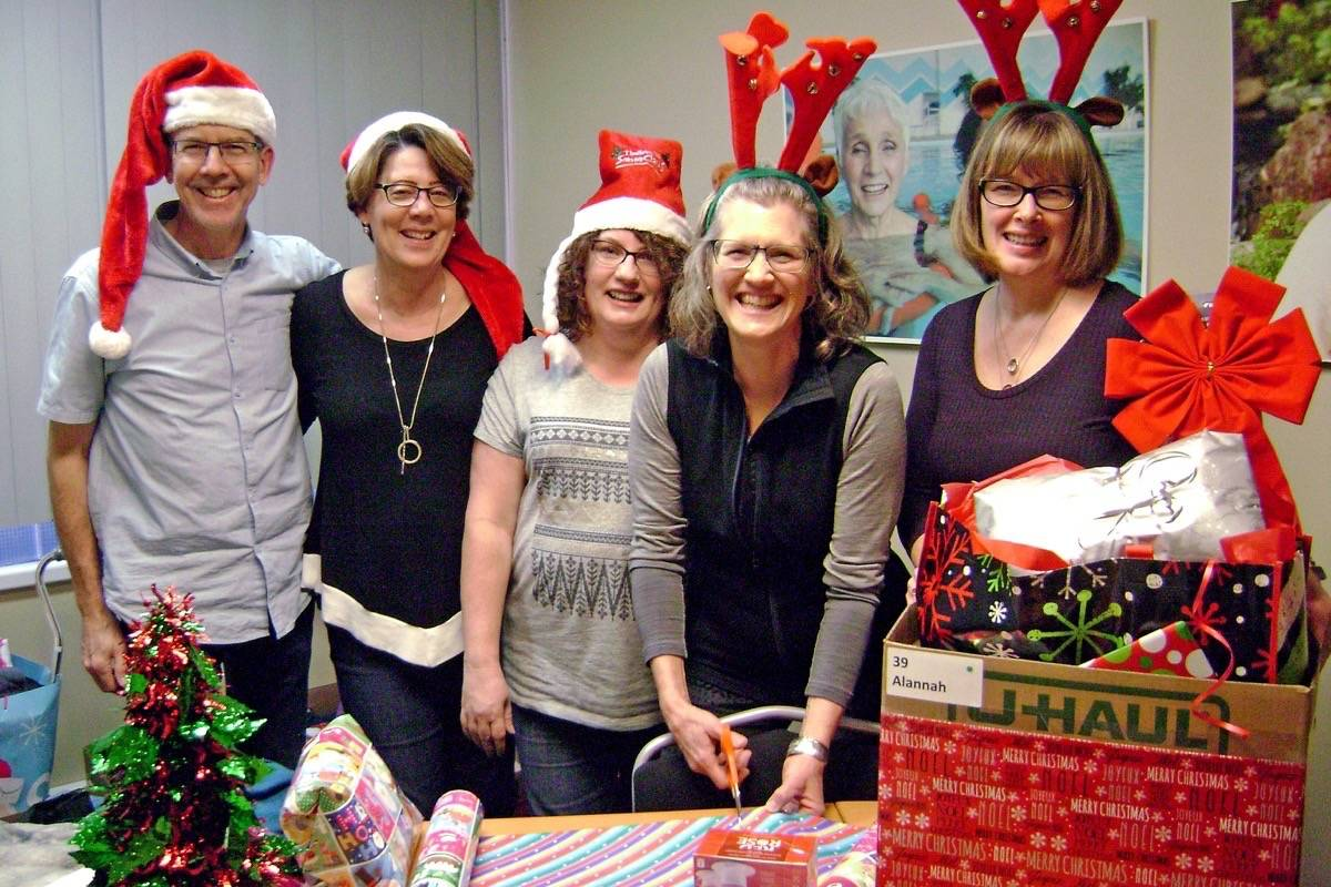 Home Instead Senior Care's (from left) Wes Colby, Diana Bonner, Lisa Bray, Nancy Colby and Laurie McPherson wrapped hundreds of gifts for recipients of the business's Be a Santa to a Senior program Monday. (Contributed photo)