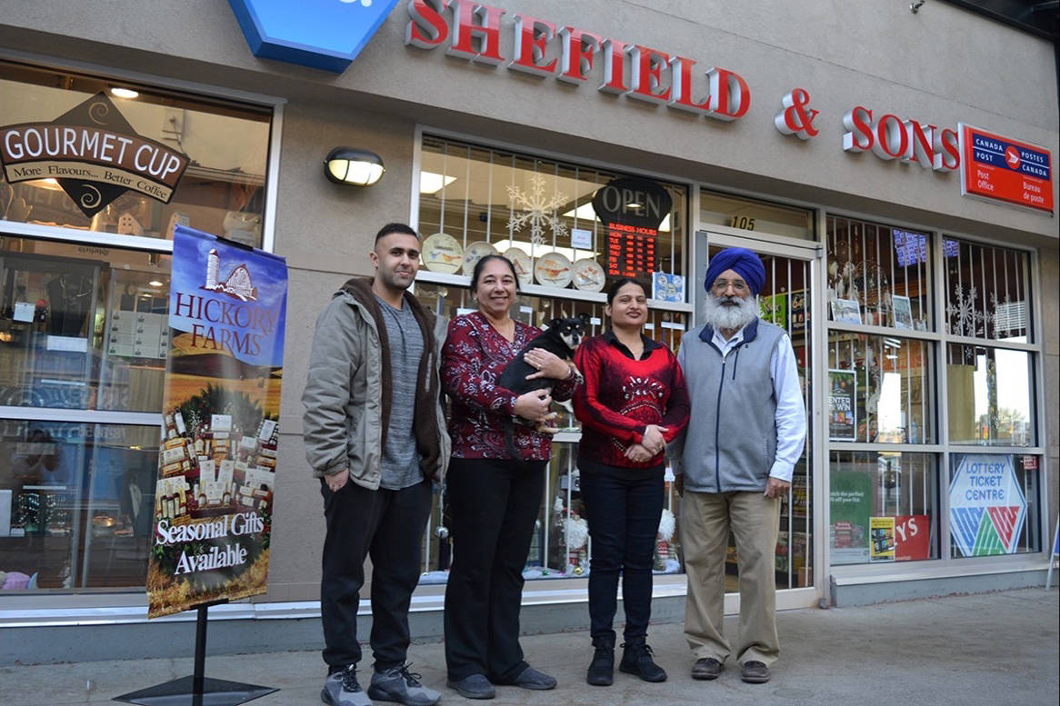 Rose Sidhu (second from left holding Ricky the dog) and her husband Harjit, (far right) are retiring from running Shefield's in Langley Mall for the past 22 years. New owner Brian Deol (outside left) with his brother Devon will take over in January. Staff member Ravinder Athwal (middle right) will stay on. Monique Tamminga Langley Times