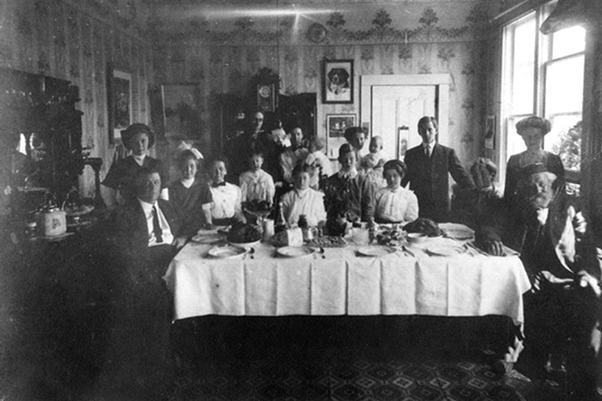 Christmas dinner at the Hadden house, 1910, located in Cloverdale on Old McLellan Road. From left: Dave Hadden, Jean Hadden, Patsy Hadden, Emma Hadden, Archie McGregor, Snny McGregor, Doug Hadden, Tini Prophet, Gertie Hadden, Willie Hadden, Laura Hadden, Louie Hadden, James Hadden. (Courtesy City of Surrey Archives / 170H06)