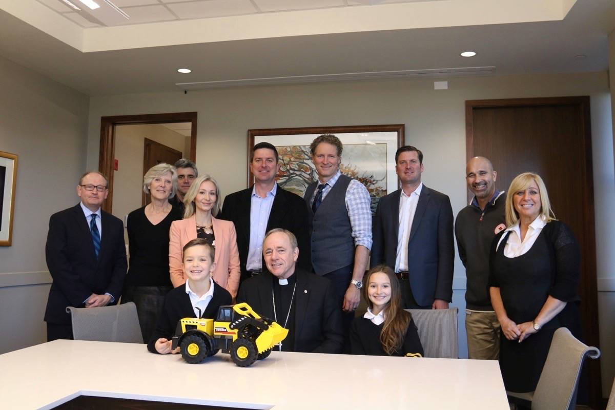 Contributed photo                                 Peter Miller, Archbishop J. Michael Miller and Troy Van Vliet (centre) with members of the Miller family, the Tavan Group and school administrators at the announcement of the site-clearing donation for St. John Paul II Academy.