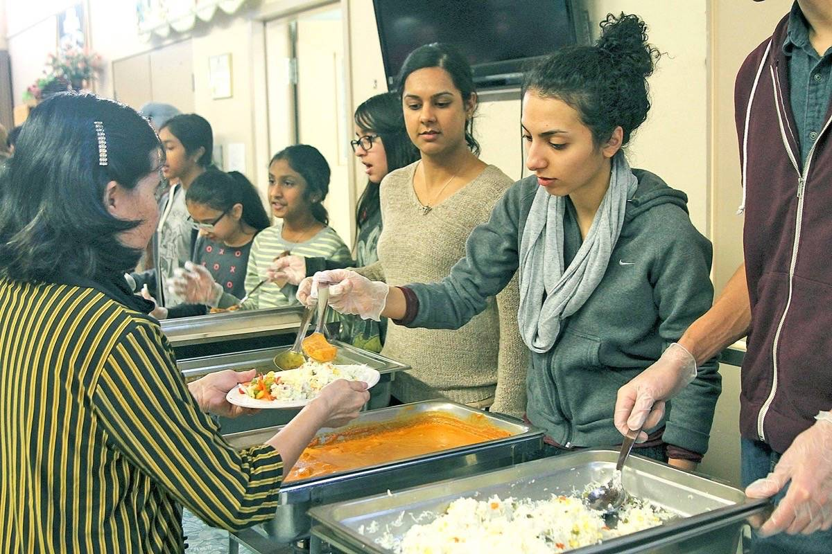 File photo                                 Volunteers serve food to guests at last year's interfaith luncheon.