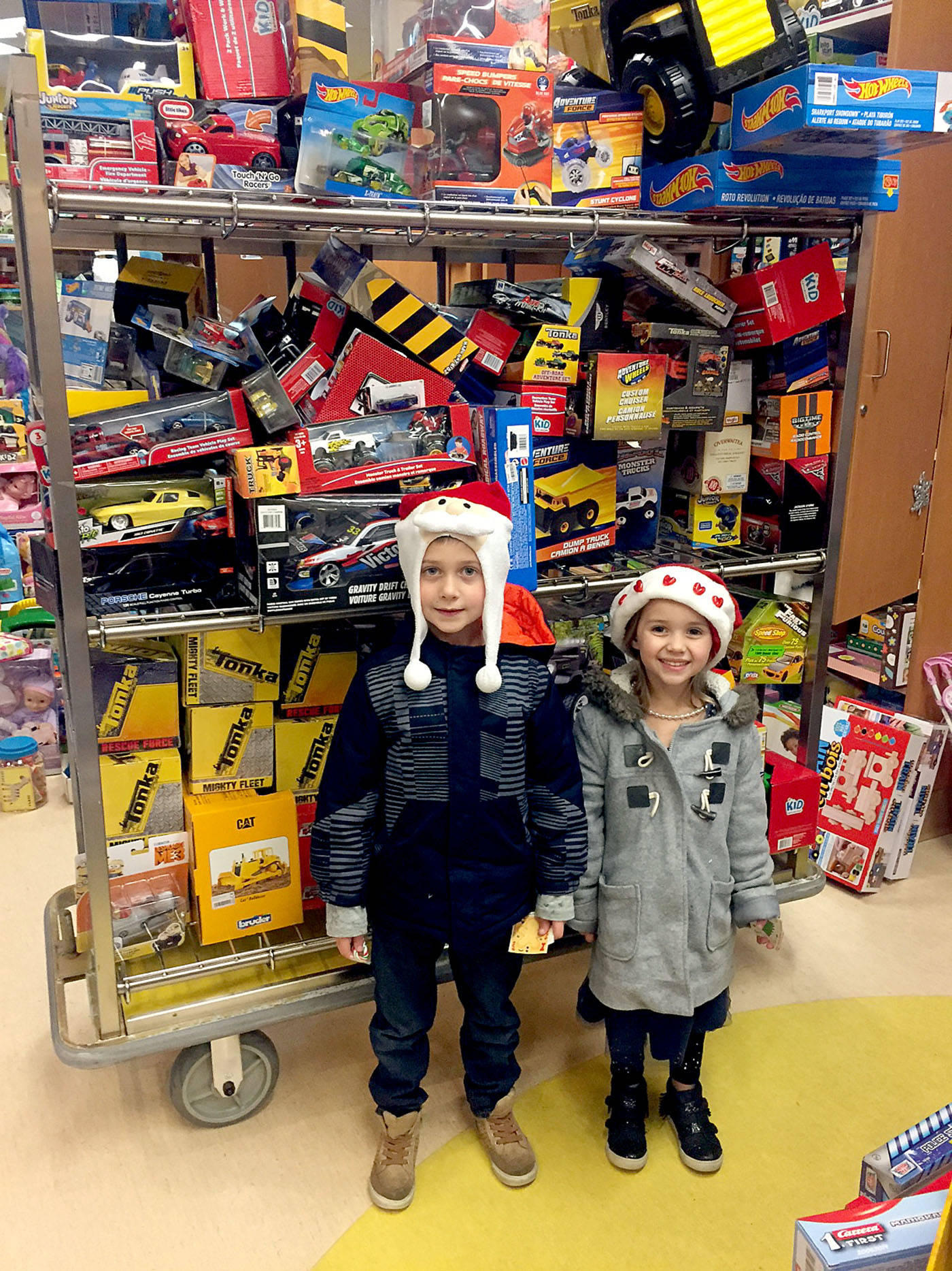 Carson Walton, six, and his kid sister Kayla stood in front of the toys they bought for young patients at BC Children's Hospital.