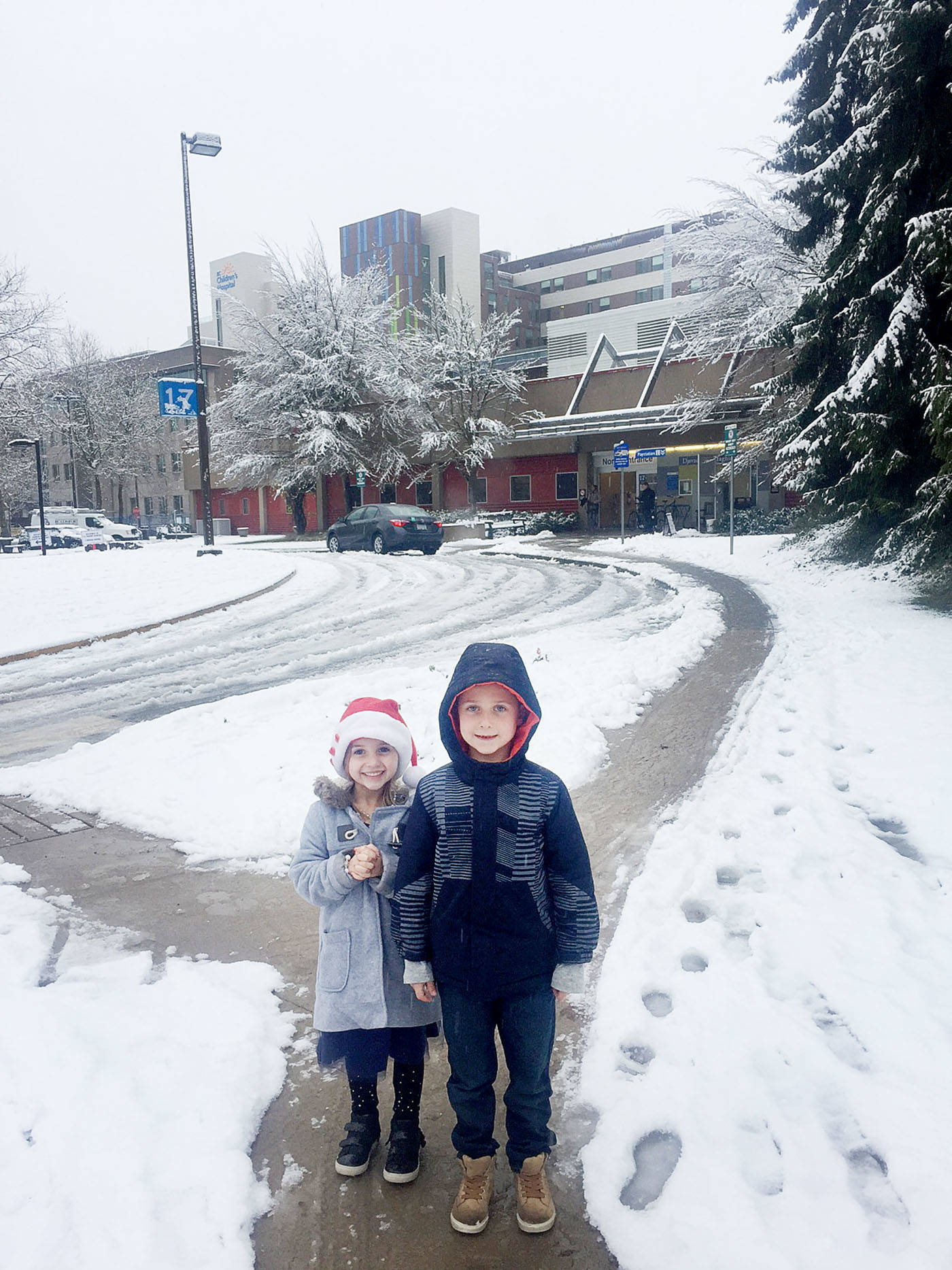 Siblings Kayla and Carson Walton stood near BC Children's Hospital, where the two joined their family to drop off presents for young patients on Tuesday, Dec. 19.