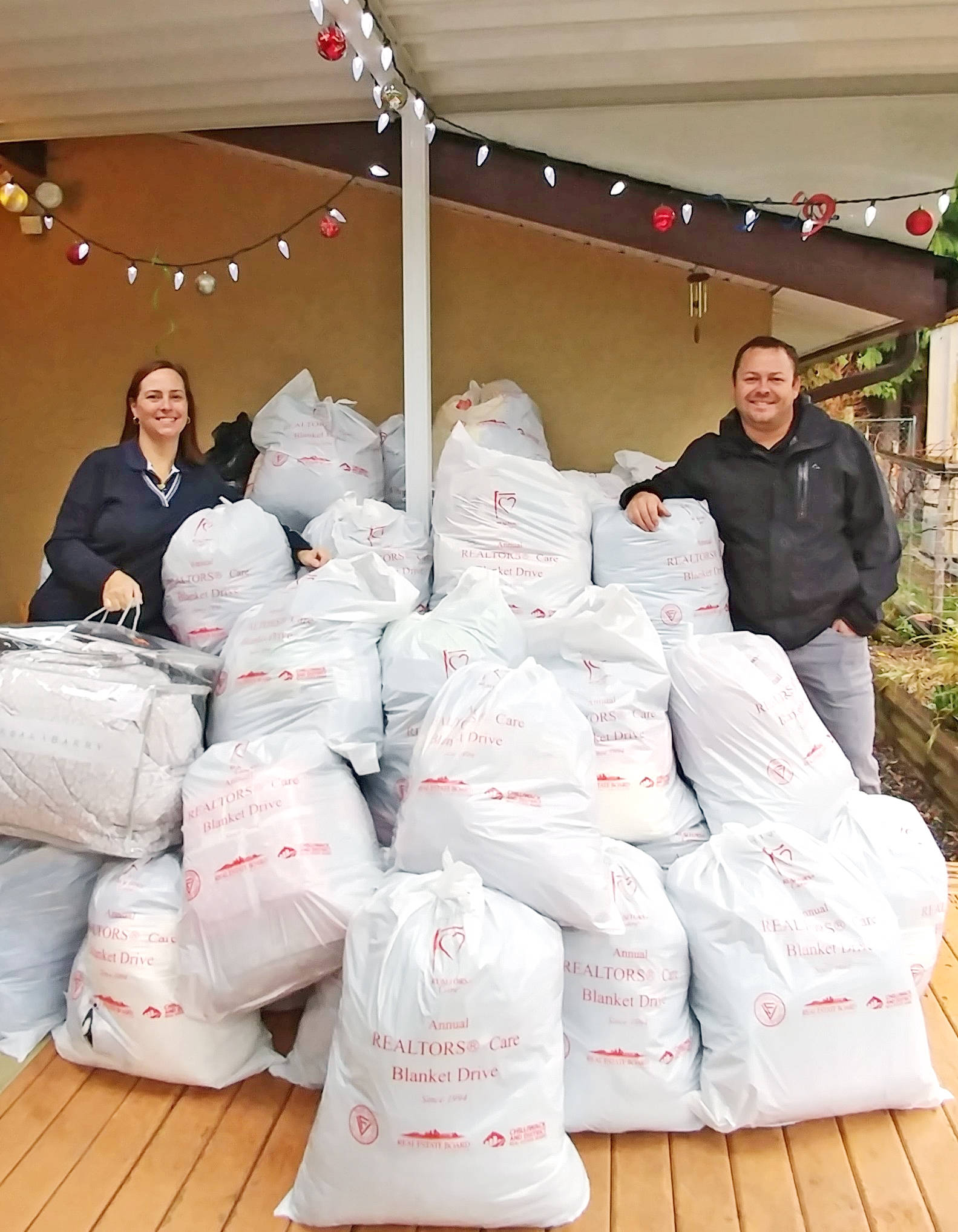 Blanket drive volunteers Cyndi Polovina and Tom Osterberg show off the large amount of donations received this year. Submitted photo