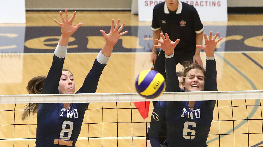 Trinity Western's Katelyn Devaney (#8) and Hilary Howe team up for the block against the Regina Cougars. Scott Stewart TWU Athletics