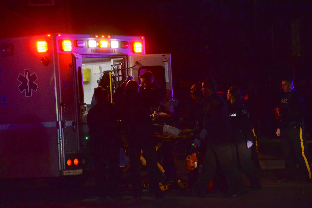 Emergency responders load a wounded man into an ambulance in Langley. RCMP received calls of shots fired in the 8200 block of 204B St Friday night. Curtis Kreklau, South Fraser News Services