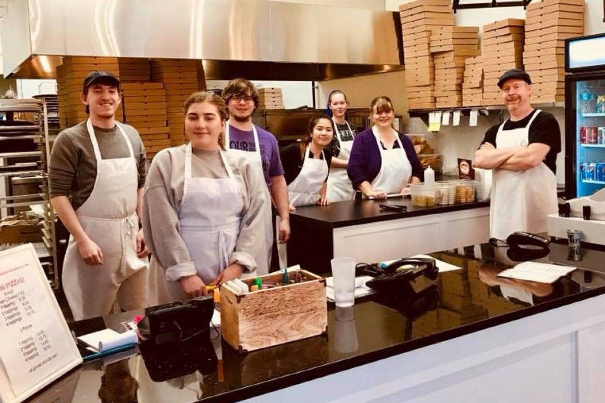 After 32 years, Jim's Pizza Fort Langley owners Emma Weslowsky (in purple) and Allan (right folding arms) have had to move locations but are making new friends at their Walnut Grove eatery located at #10-20349 88 Ave. Same great pizza, same staff pictured here in their new digs. Submitted picture