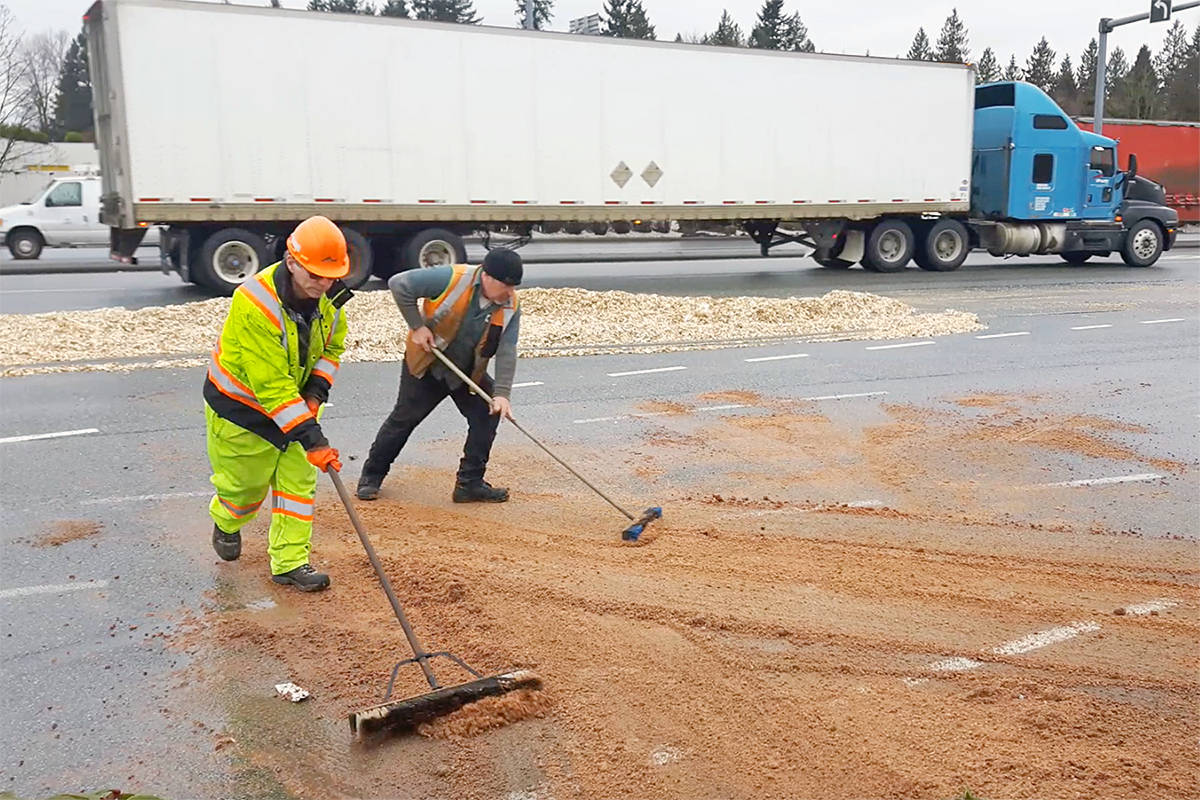 Workers clean up debris left by a multi-vehicle crash on 200 Street just north of the Hwy. 1 overpass. Dan Ferguson Langley Times
