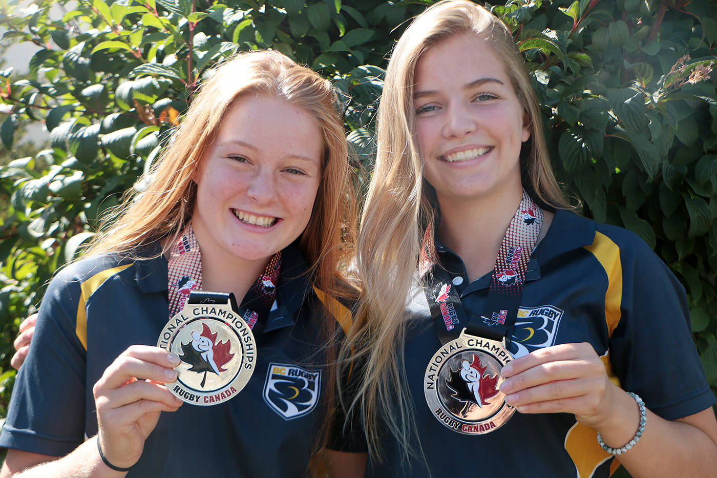 Samantha Lillywhite and Mikayla Brennan-McCann display their silver medals from the 2017 Canadian Rugby Championships. Both girls are headed to Vegas with BC Elite Youth Sevens teams this week. (Citizen file)