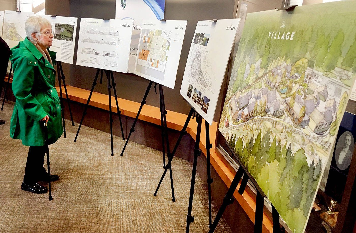 A visitor to The Village's reception and presentation at the Township Civic Facility on Wednesday looked at plans and an artist's rendering of the future memory care community being built in Brookswood.                                 Troy Landreville Langley Times