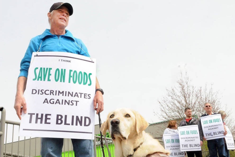 Joined by his service dog Gretel and a handful of supporters, Matt Salli picketed outside the Walnut Grove Save-On-Foods on Thursday afternoon. Troy Landreville Langley Times