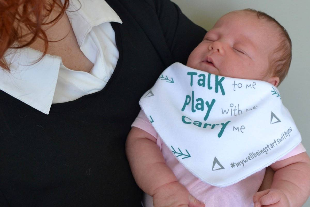Langley mom Kimberley Chalmers with her four-week-old daughter Kamaria who proudly wears the Langley Child Development designed bandana that says 'talk to me, play with me, carry me' to encourage parents to put the phone down and interact with their babies. Monique Tamminga Langley Times