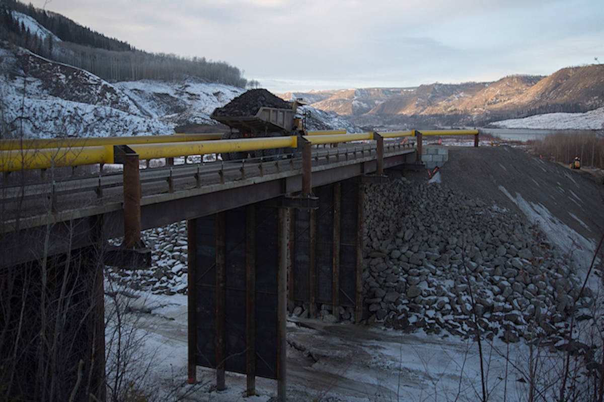 Truck hauls material across temporary bridge built across the Peace River for construction of the Site C dam, January 2017. /BC HYDRO