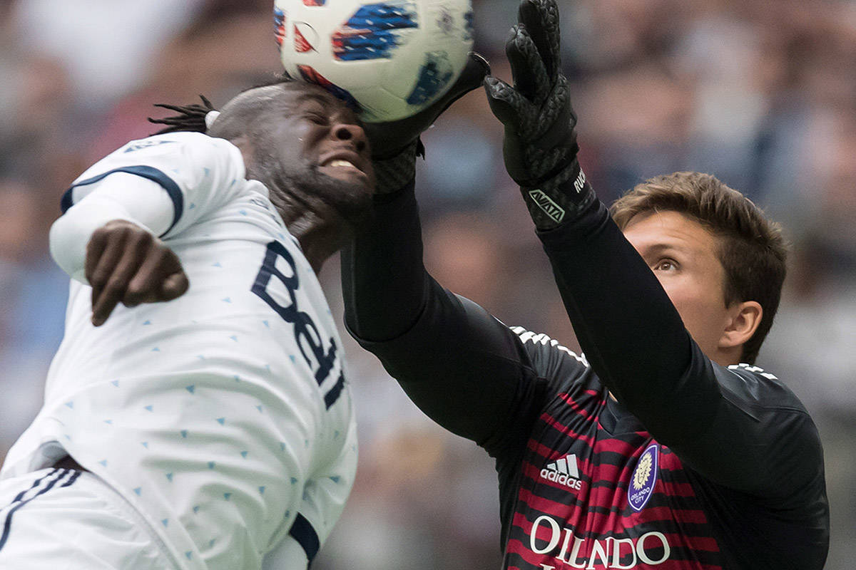 Orlando City goalkeeper Joe Bendik, right, grabs the ball away from Vancouver Whitecaps' Kei Kamara as he attempts to get his head on it during the second half of an MLS soccer game in Vancouver, on Saturday June 9, 2018. THE CANADIAN PRESS/Darryl Dyck