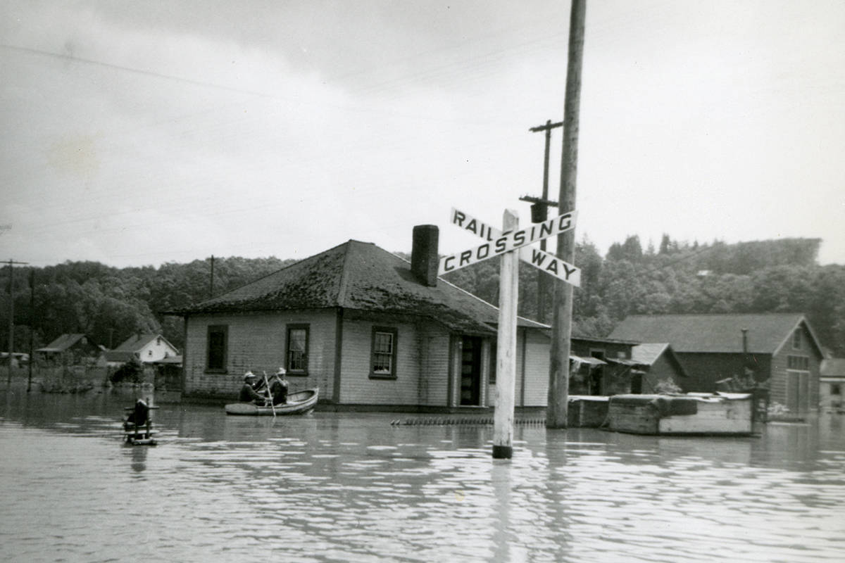 A flood at the Port Mann and the Canadian National Railway shops. Men are in the water, a house, and a railway crossing sign are shown in the flooded area. (Photo courtesy of the City of Surrey Archives / SMA89.064.004)