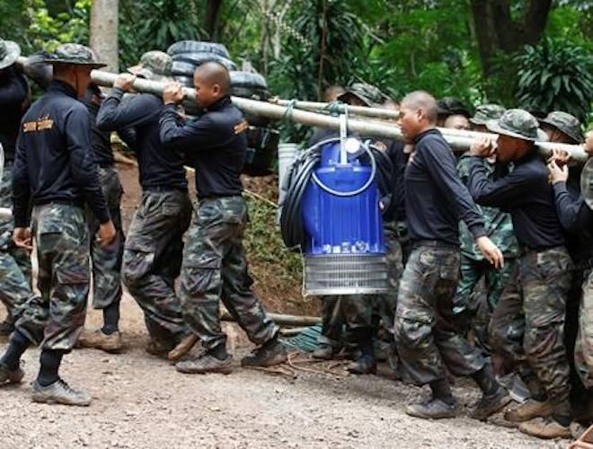 Soldiers carry a pump to help drain the rising flood water in a cave where 12 boys and their soccer coach have been trapped since June 23, in Mae Sai, Chiang Rai province, in northern Thailand Friday, July 6, 2018. (AP Photo/Sakchai Lalit)