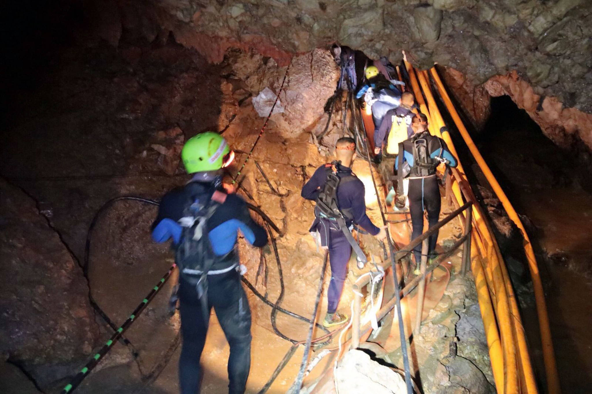 In this undated photo released by Royal Thai Navy on Saturday, July 7, 2018, Thai rescue team members walk inside a cave where 12 boys and their soccer coach were trapped since June 23, in Mae Sai, Chiang Rai province, northern Thailand. (Royal Thai Navy via AP)