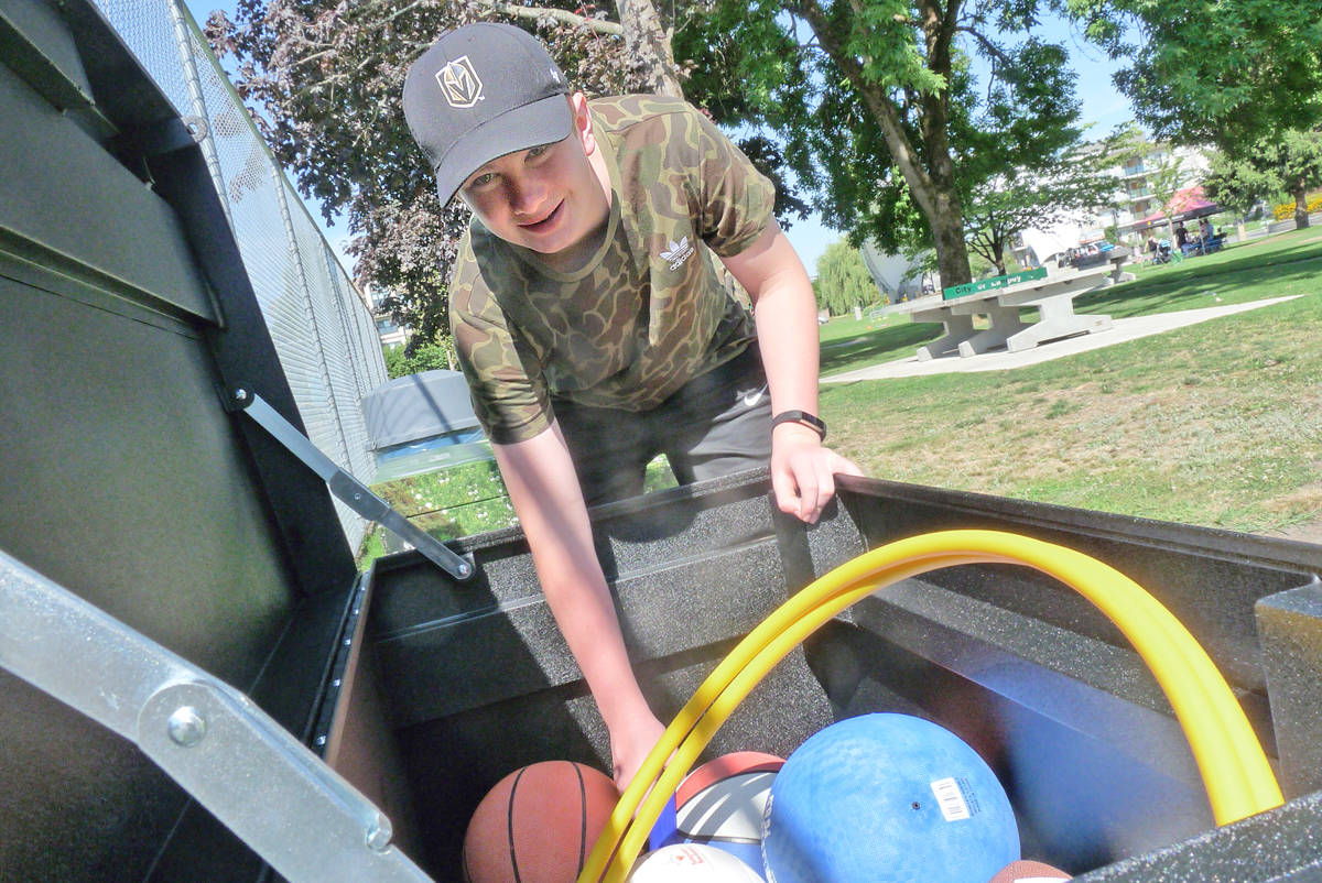 Sam Brown checks out the contents of a newly-installed Langley City playbox in Douglas Park. Dan Ferguson Langley Times