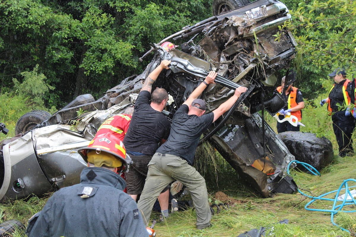 Motorists and emergency personnel rescue occupants of a truck in a Saturday afternoon crash on the Island Highway. Scott Stanfield photo