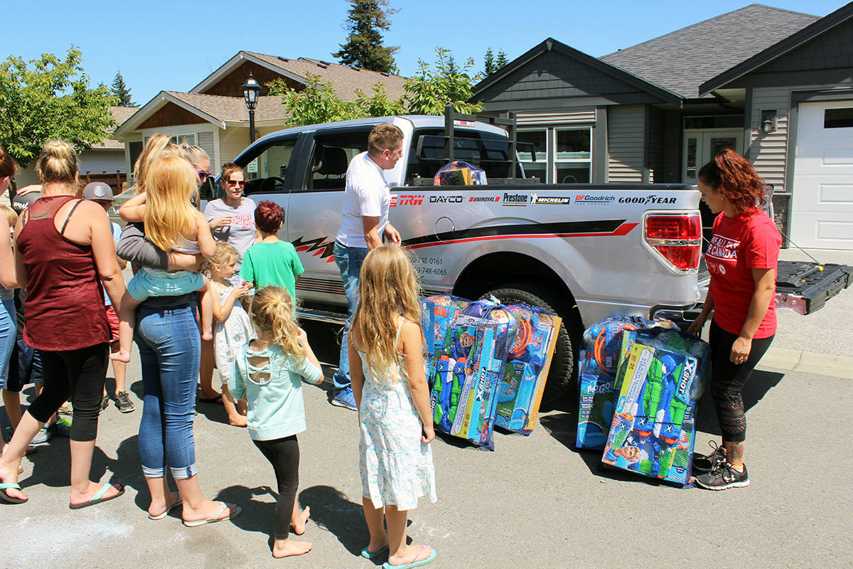 Kids in the Artisan Gardens subdivision receive toys, games and inflatable pools donated by Canadian Tire. (Photo by Don Bodger)