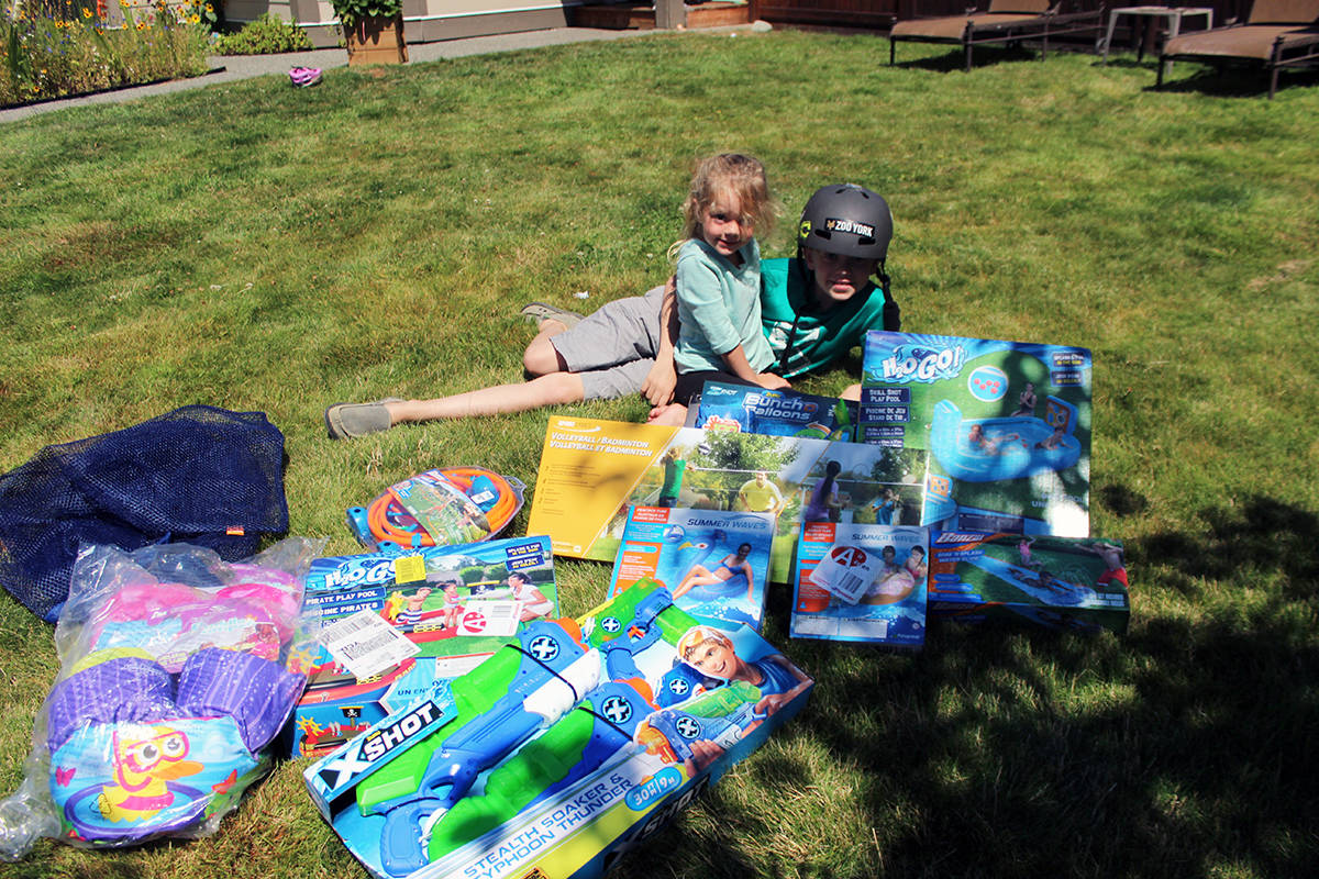 Aubree Germiquet and Hayden Germiquet spread the toys on the lawn they received from Canadian Tire in the Chemainus neighbourhood where kids' street play was banned due to a strata bylaw. (Photo by Don Bodger)