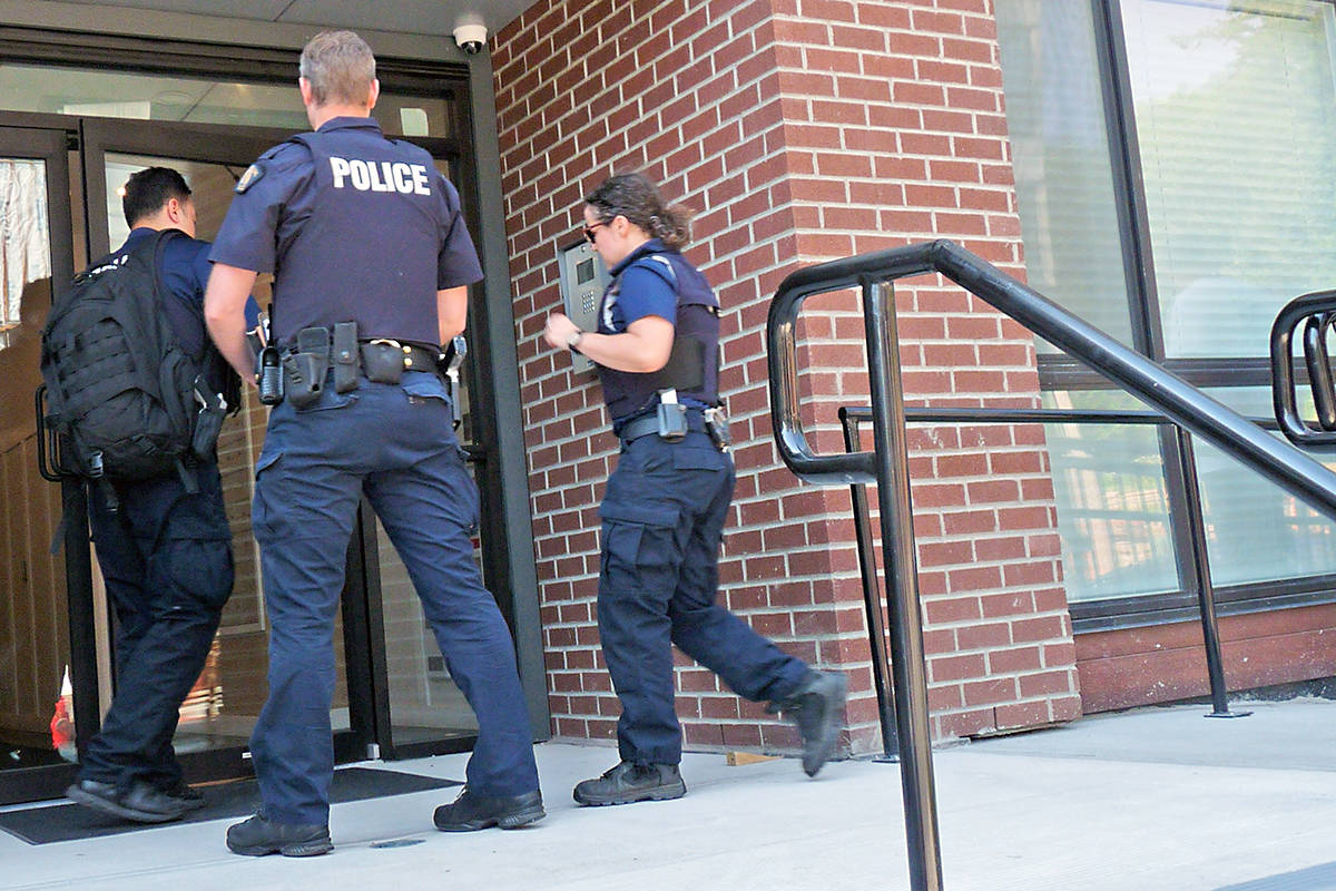 Police officers enter a building where a seven-year-old girl was found dead. Dan Ferguson Langley Times