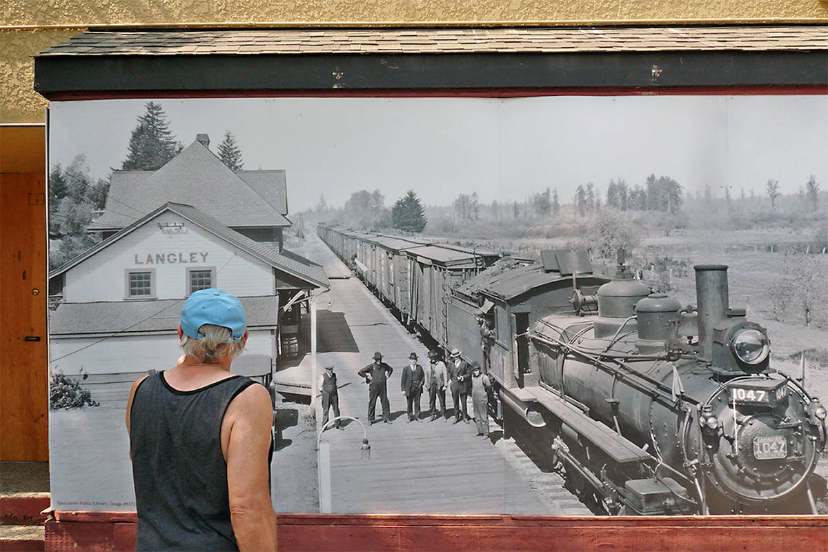 A passer-by checks out one of the historic photos placed on boarded-up buildings in Fort Langley by developer Eric Woodward. Dan Ferguson Langley Times