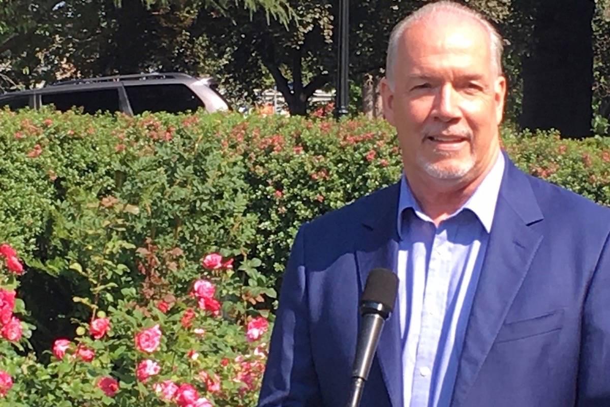 Premier John Horgan takes questions at the B.C. legislature rose garden, July 30, 2018. (Black Press)