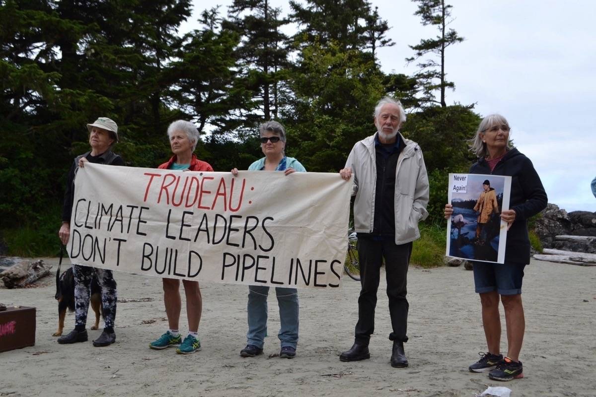 Tofino locals stand in solidarity on July 31 at Cox Bay Beach against the purchase and construction of the Trans Mountain pipeline. (Nora O'Malley / Westerly News)