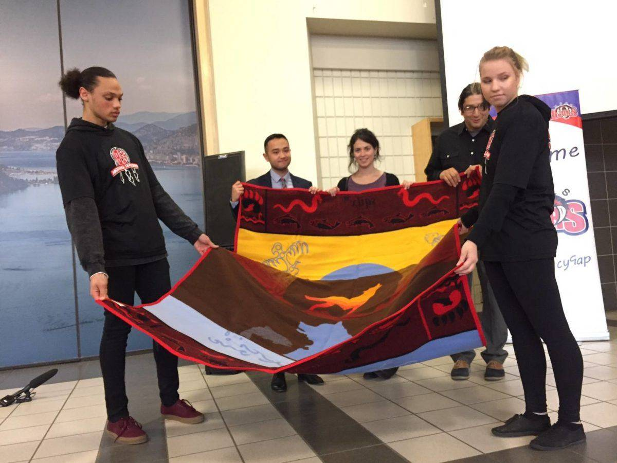 Photo Credit: Barry Gerding/Black Press                                Traditional ceremonial blanket is presented to representatives of the EdCan Network last fall at Mount Boucherie Secondary School. EdCan presented a financial award to the school for its successful effort to launch an Indigenous student academy.