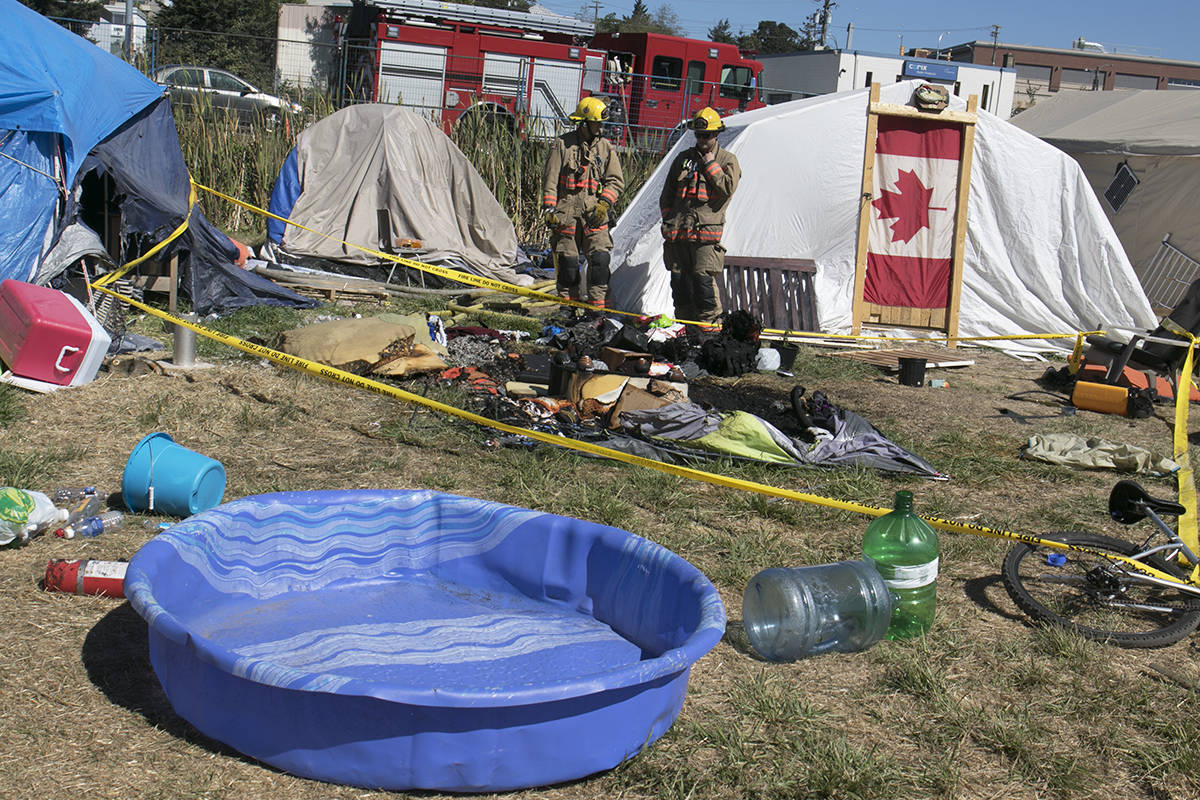 Firefighters from Saanich Fire Department survey the damage to a tent in Regina Park after a fire broke out Sunday shortly after 12 p.m. No one was in the tent at the time of the blaze and no injuries were reported. Kristyn Anthony/VICTORIA NEWS