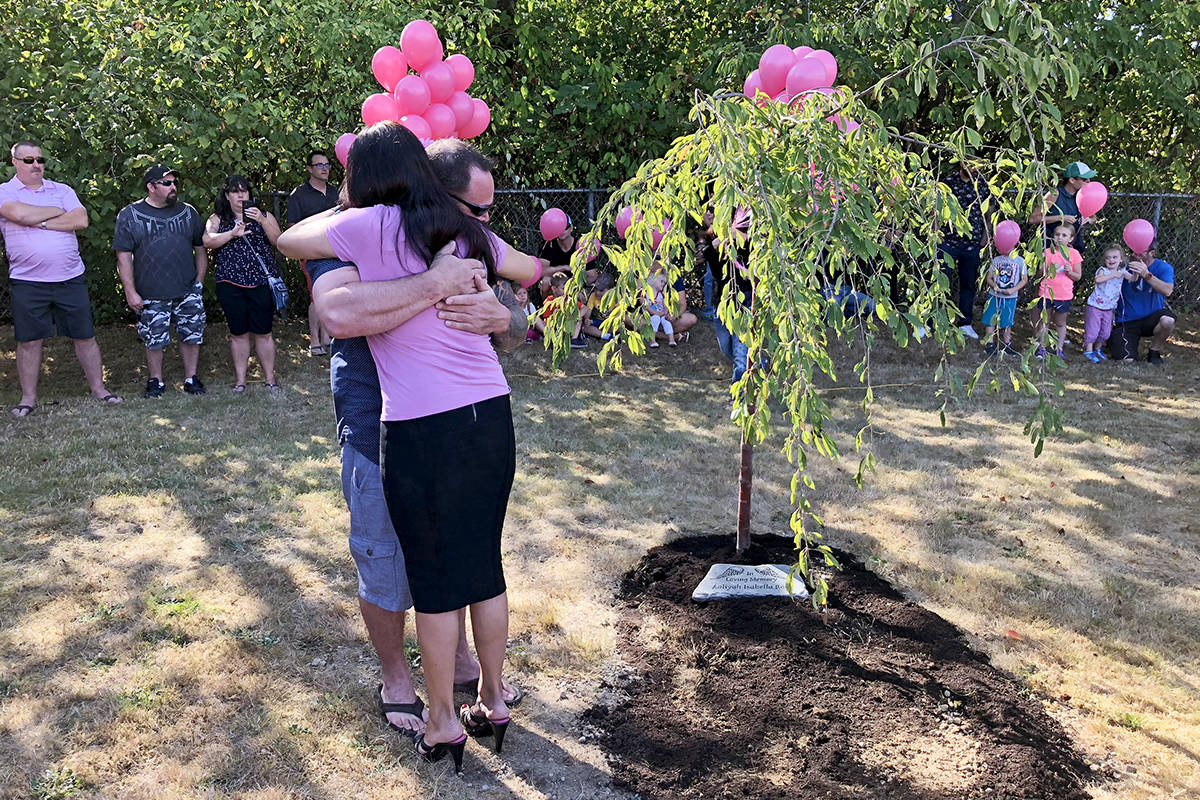Aaliyah Rosa's father, Steve, is comforted by one of the young girl's former teachers during a tree of life planting ceremony on Monday. Photo courtesy Sunflower Montessori