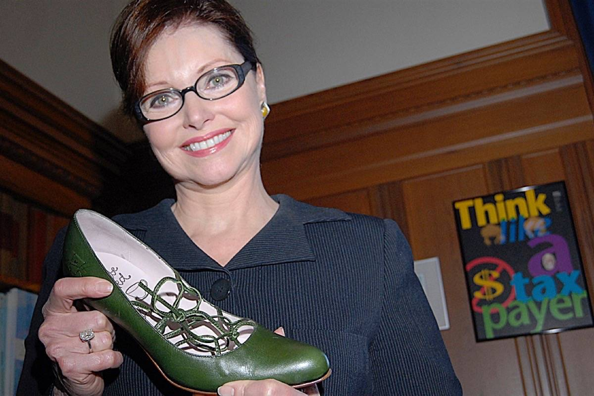 Former finance minister Carole Taylor shows her green budget shoes the day before introducing B.C.'s carbon tax, February 2008. (Tom Fletcher/Black Press)