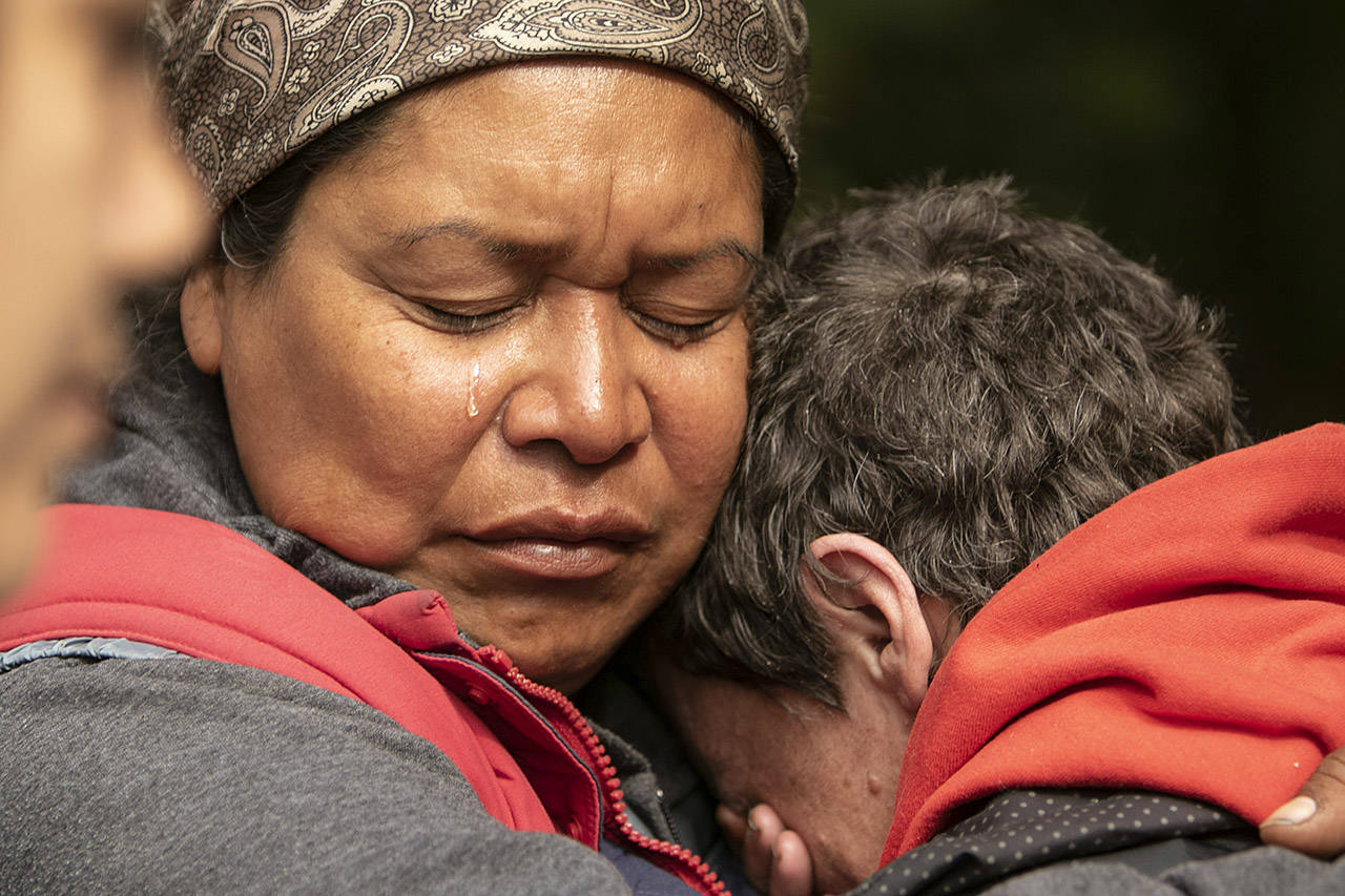 Chrissy Brett weeps as she holds another Camp Namagens resident at Goldstream Park in Langford (Arnold Lim/Black Press)