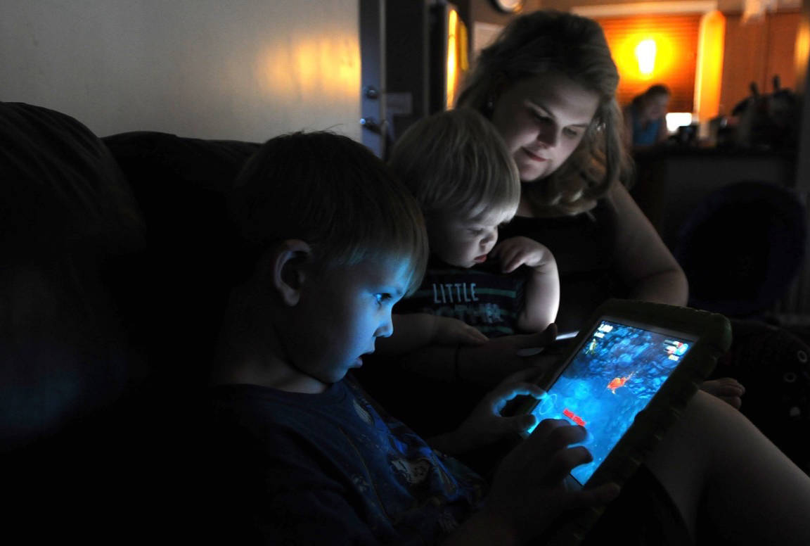 The Smirnov family: (from left) Leonardo, 5, Dominik, 18 months, and mother Samantha, with their iPads.                                (Colleen Flanagan/                                THE NEWS)