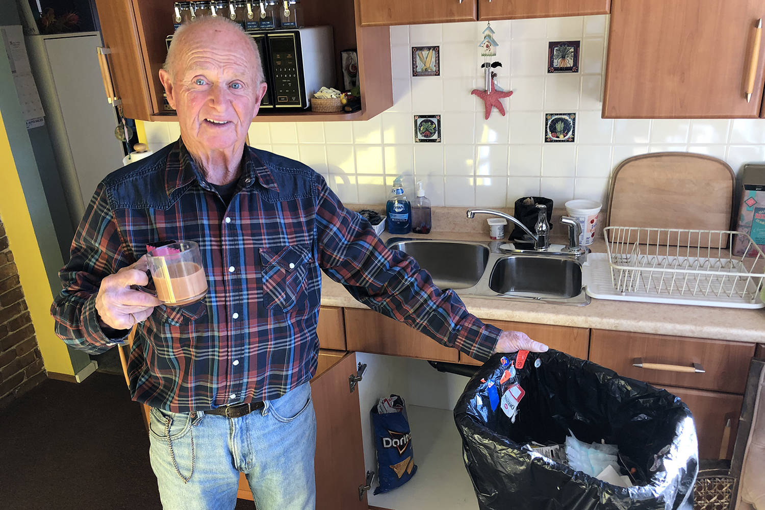 Dust flies off the contents of Ken Wardroper's garbage can he keeps under the sink. The can remains half empty, still not full after three years. (Travis Paterson/News staff)