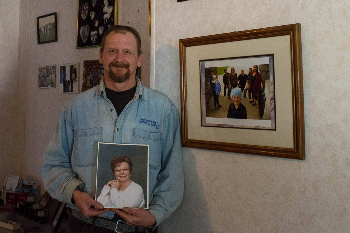 Ross Hurlbert holds a photo of his mother Caroline Hurlbert with pictures of his roommate's family are in the background. Usually all of them spend Christmas together. However, this Christmas may be different (Liam Harrap/Revelstoke Review).