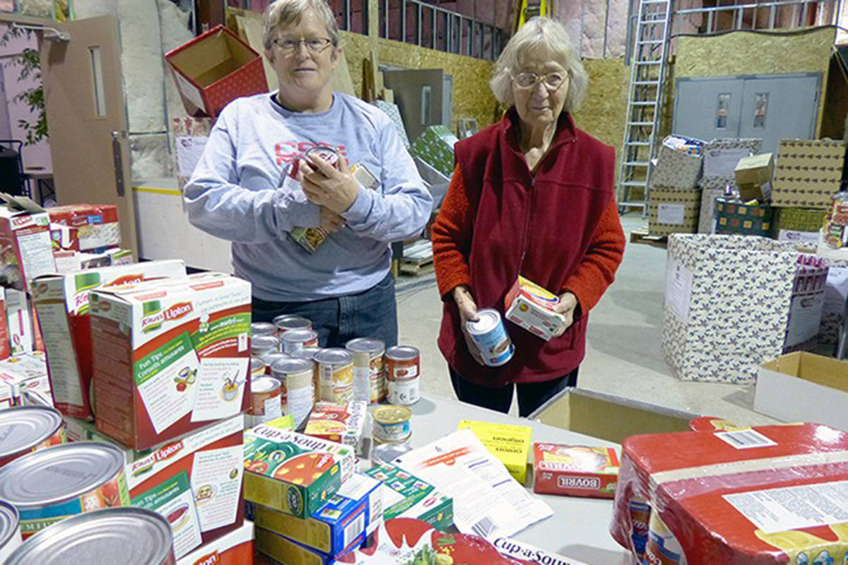 Cloverdale Christmas Hamper Program volunteers Sandy Doyle and Marie Kovacs finish up the afternoon shift at Pacific Community Church in this file photo from December 2013. (Jennifer Lang)