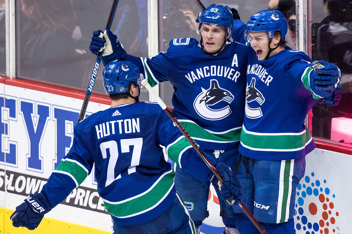 Vancouver Canucks' Jake Virtanen, right, celebrates his second goal with teammates Bo Horvat, back left, and Ben Hutton during the second period of an NHL hockey game against the Chicago Blackhawks in Vancouver, on Wednesday October 31, 2018. THE CANADIAN PRESS/Darryl Dyck