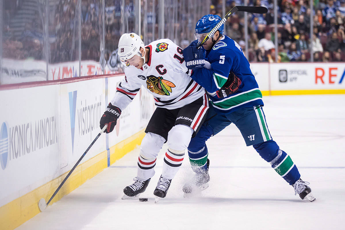 Vancouver Canucks' Derrick Pouliot (5) checks Chicago Blackhawks' Jonathan Toews (19) during the first period of an NHL hockey game in Vancouver, on Wednesday October 31, 2018. THE CANADIAN PRESS/Darryl Dyck