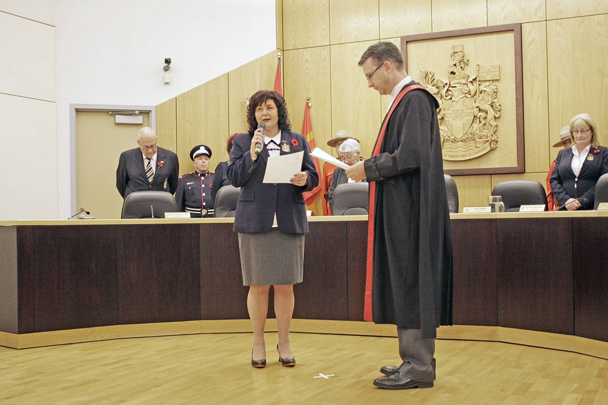Judge Rob Hamilton administers the oath of office to new Langley City mayor Val van den Broek. Dan Ferguson Black Press