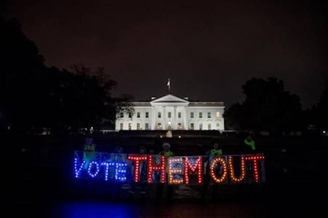 """A group of people hold up a sign that reads """"Vote Them Out"""" as they protest in front of the White House the night before midterm election voting begins, Monday, Nov. 5, 2018, in Washington. (AP Photo/Andrew Harnik)"""