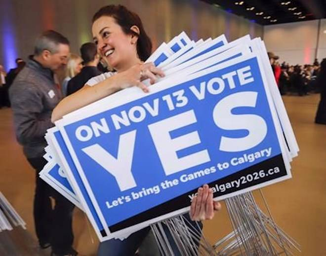 Tabetha Boot carries lawn signs during a rally in support of the 2026 Winter Olympic bid in Calgary, Alta., on November 5, 2018. THE CANADIAN PRESS/Jeff McIntosh