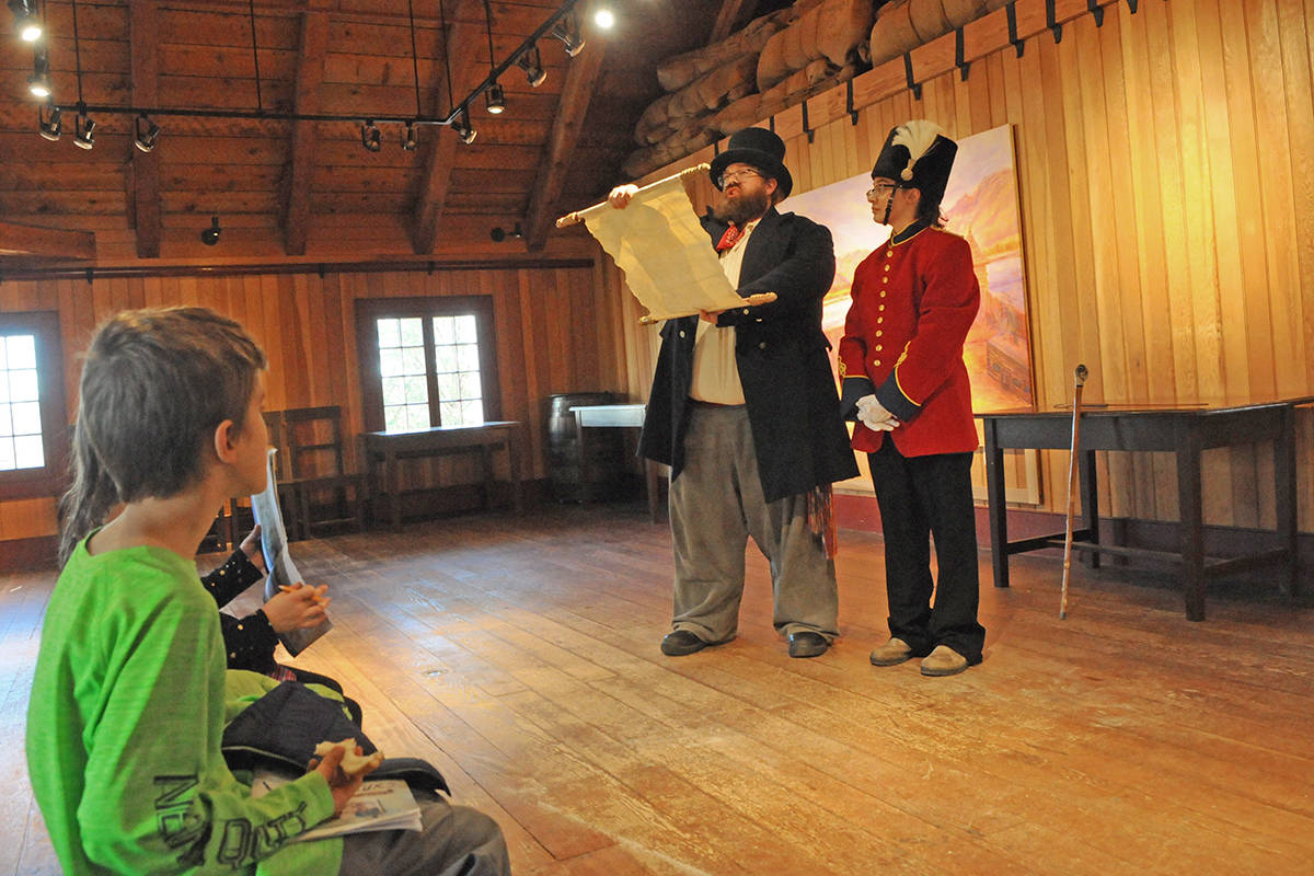 Sir James Douglas, portrayed by Joe Daniels reads the announcement proclaiming creation of British Columbia while Colonel Richard Moody, played by Chloe Heuchert, looks on. The skit was part of Douglas Days at historic Fort Langley on Sunday. Black Press photo