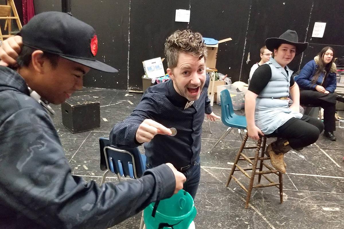 Theatre teacher Patrick McMath makes a contribution to student Dwayne Melendez. Black Press photo