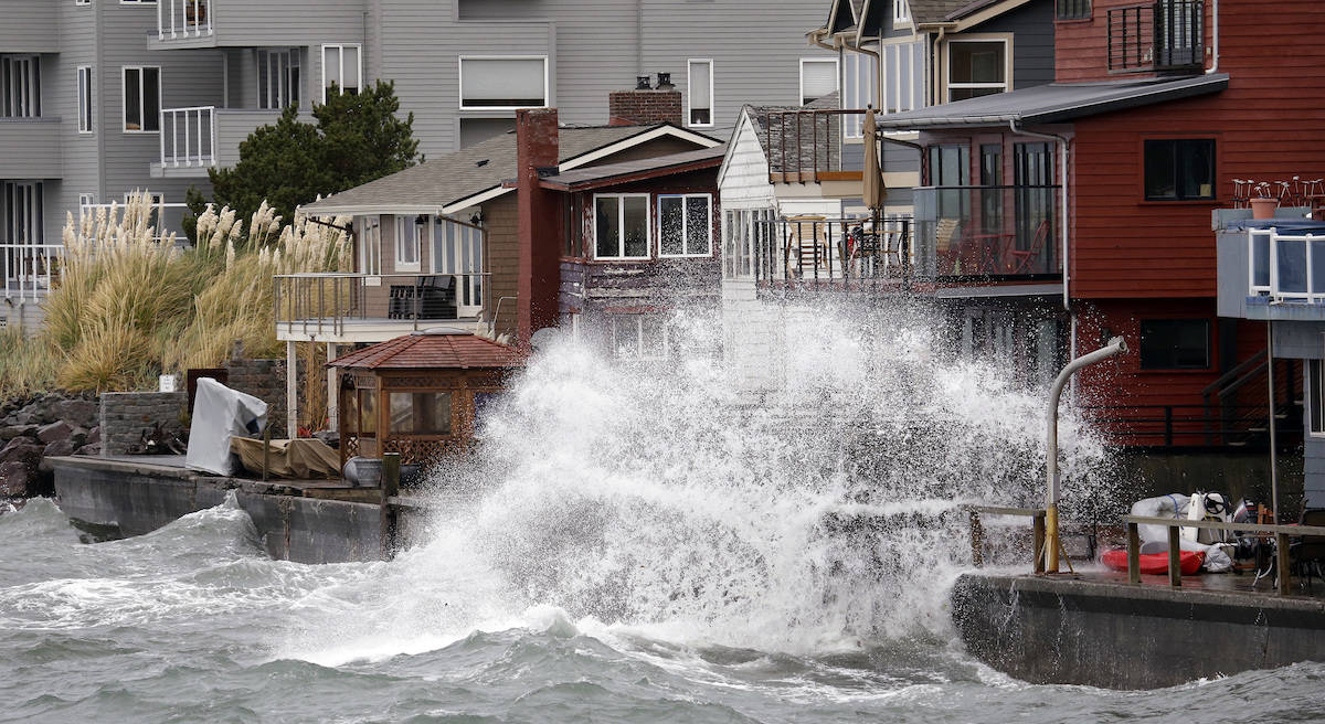 Waves hitting a breakwater send salt spray onto homes along Puget Sound in a windstorm Monday, Nov. 13, 2017, in Seattle. File photo. (AP Photo/Elaine Thompson)