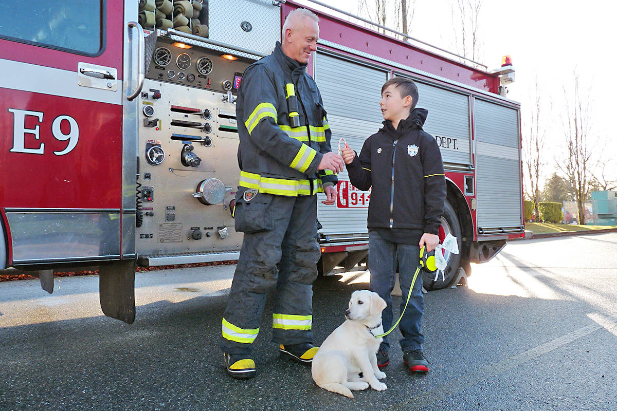 Devon Levere and his dog Chloe met firefighter Tim Warkentin as the annual Candy Cane run got underway in Murrayville. Black Press photo